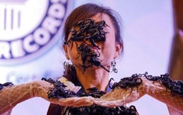 بالصور.. فتاة تايلاندية تحطم الرقم القياسي لإبقاء العقارب في فمها