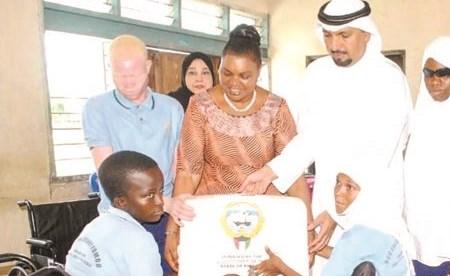 السفير جاسم الناجم والوزيرة جينستا مهاغاما يسلمان إحدى النزيلات ماكينة خياطة خاصة لذوي الإعاقة