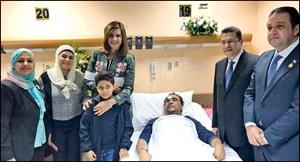 الوزيرة نبيلة مكرم خلال زيارتها المواطن المصري بحضور السفير المصري وأسرة المصاب (أحمد علي)