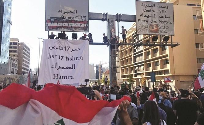 المتظاهرون يرفعون لافتة تحمل اسم جسر 17 تشرين الأول فوق جسر الرينغ أمس