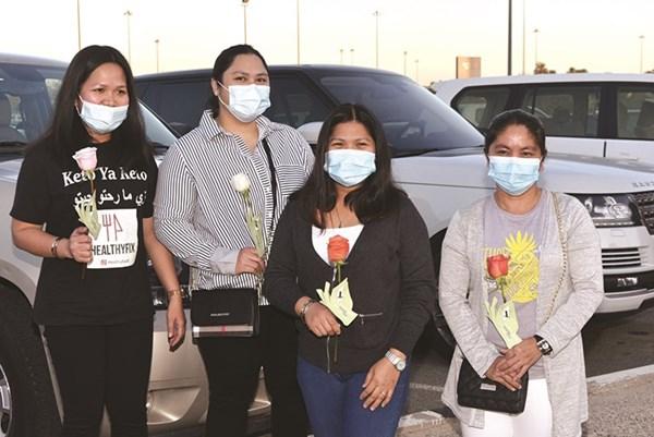 عدد من العمالة المنزلية بعد توزيع الورود عليهم