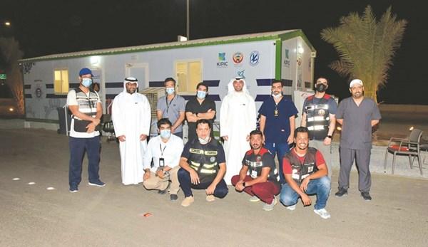 موظفو بنك بوبيان مع العاملين في مركز تطعيم جسر الشيخ جابر